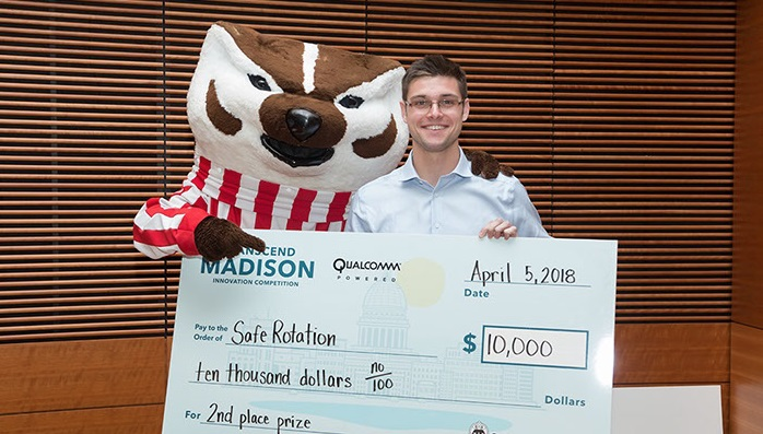 Shawn Michels posing with Bucky Badger in front of a large check for $10,000, the 2nd place prize in the Transcend Madison competition.