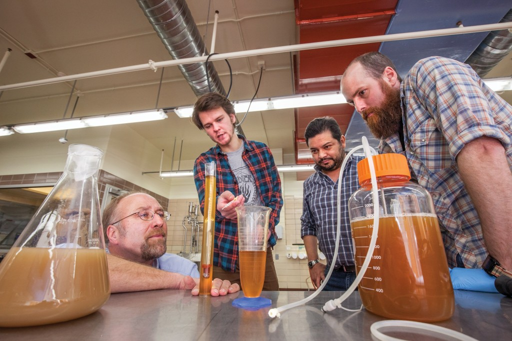 Photo of Jim Steele with a group of students examining fermenting beer on a table in various test tubes and fermentation jars.