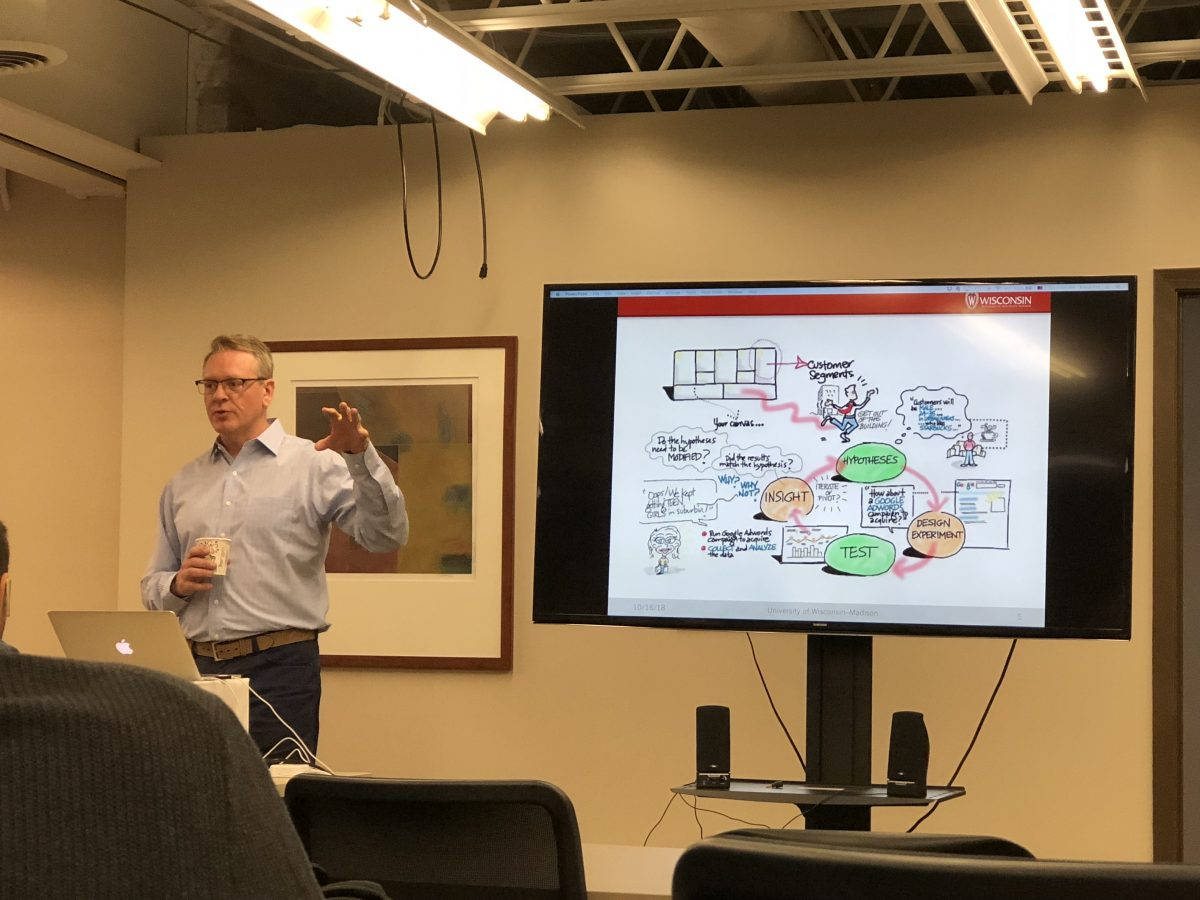 David Ertl gestures next to a slide showing a sketched diagram about determining a customer segment. It shows a cycle between hypothesis, design experiment, test, and insight.
