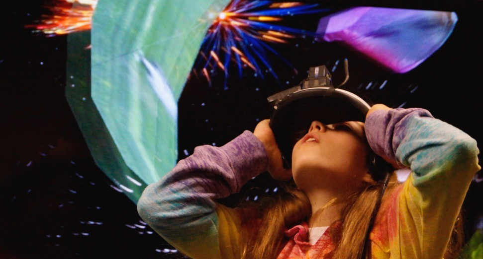 A kid looks through a virtual reality device at a colorful display