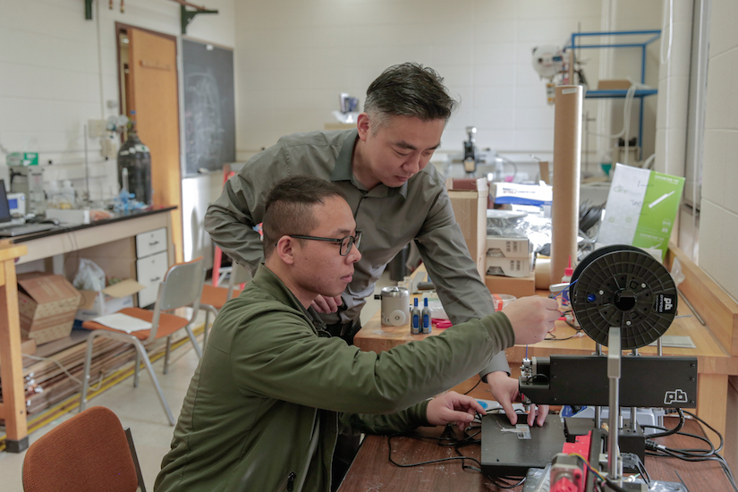 Graduate student Guang Yao (seated) and principal investigator Xudong Wang (standing) make adjustments to a 3D printer that was used to fabricate implantable weight-loss devices. Photo credit: Sam Million-Weaver.