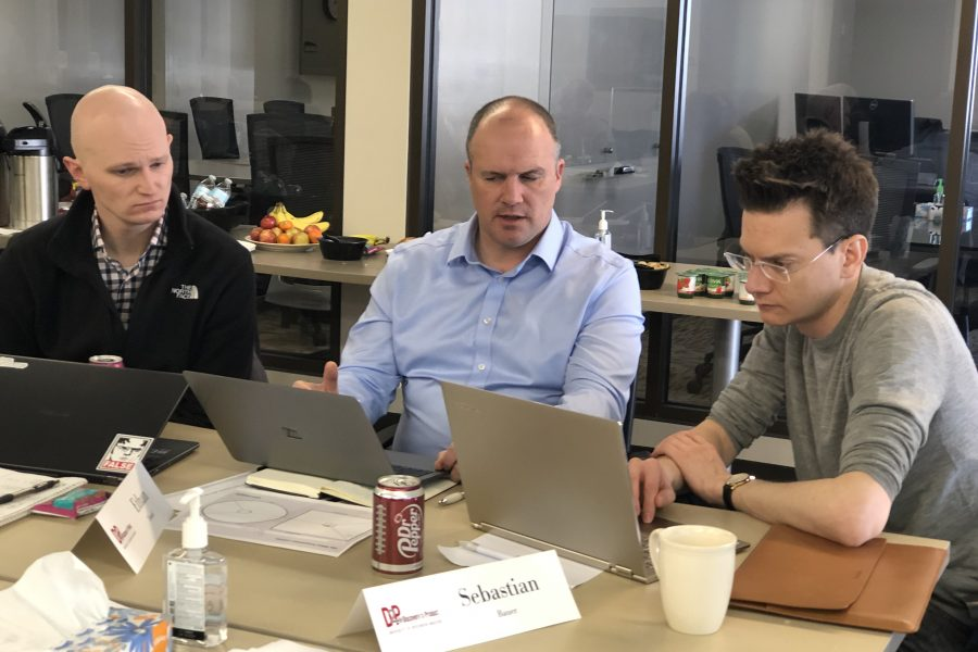 Three men discussing information they are looking at on computer screens.