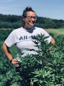 Kattia Jiménez next to one of the hemp plants on her farm.