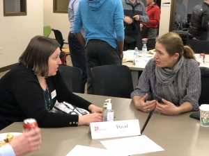 Two women at a table discussing an issue